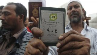 Foreign workers hold up their passports outside a labour office in Riyadh (4 November 2013)