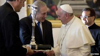 Pope Francis (L) talks with Israeli Prime Minister Benjamin Netanyahu as he was presented with a Menorah during a private audience at the Vatican December 2, 2013