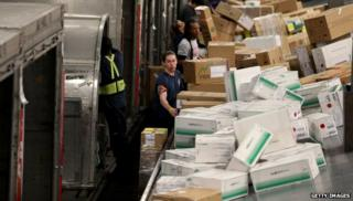 Workers with packages on an assembly line