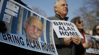 Supporters of Alan Gross, seen on poster at left, hold an event to mark his fourth year in prison in Cuba, 3 December 2013