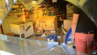 A worker cleans a looted a supermarket on 3 December 2013 in Cordoba
