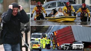 Composite image of a man holding onto his hat in the wind, a couple being rescued from their home by boat and police inspecting an overturned lorry which has crushed two cars