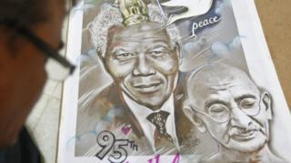 Indian artist Aejaz Saiyed works on a poster featuring the portraits of Nelson Mandela (L) and Mahatma Gandhi on Mandela's 95th birthday in the western Indian city of Ahmedabad July 18, 2013.