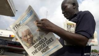 A man in Lagos, Nigeria, reads an newspaper with a front page featuring Nelson Mandela's death.