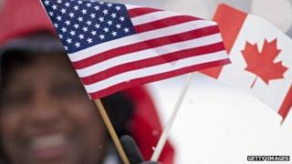A spectator waves Canadian and American flags before a meeting between US President Barack Obama and Canadian Prime Minister Stephen Harper in 2009.