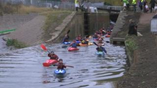 A group of kayakers move out of Dudbridge Upper Lock, Stroud