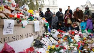 Floral tributes by Nelson Mandela statue in Parliament Square on 7 December 2013