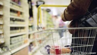 Woman in a supermarket holding a shopping basket.