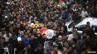 Palestinians carry the body of Wajdi Wajih al-Ramahi during his funeral in the Jalazoun refugee camp near the West Bank city of Ramallah