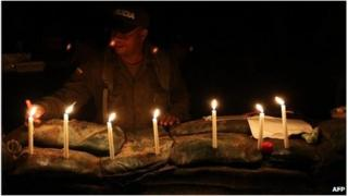 Colombian policeman lights candles for dead colleagues in Inza, Cauca