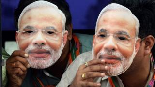 """Indian supporters of the Bharatiya Janata Party(BJP) wear masks of Gujarat state Chief Minister and the BJP""""s prime ministerial candidate, Narendra Modi, as they travel in a bus towards the airport to receive him in Mumbai on September 30, 2013."""