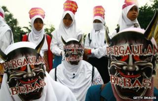 Indonesian Muslim women from Hizb ut-Tahrir Indonesia protest against condoms