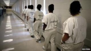 Women walk along a corridor at the Los Angeles County women's jail in Lynwood, California on 26 April 2013