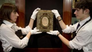 Two people wearing white gloves hold a portrait of Jane Austen