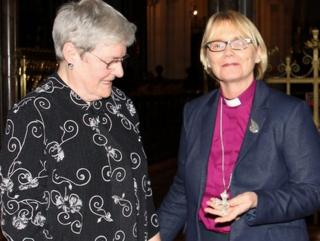 Julia Turner presents her mother's silver cross to Bishop Pat Storey, the first woman to be consecrated as a Church of Ireland bishop