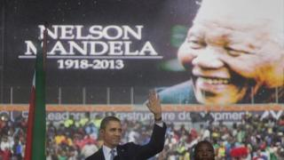 President Barack Obama waves as he arrives to speak at the memorial service for former South African president Nelson Mandela at the FNB Stadium in the Johannesburg, South Africa township of Soweto, Tuesday, Dec. 10, 2013.