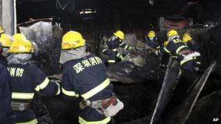 Firefighters clear debris from a market damaged by fire in Shenzhen in south China's Guangdong province, 11 December 2013