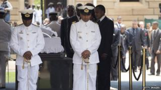 Congo's President Denis Sassou-Nguesso stands by Nelson Mandela's coffin to arrives to bid farewell to South African former president Nelson Mandela lying in state at the Union Buildings in Pretoria on December 11, 2013