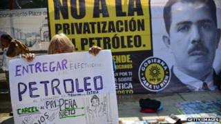 Protesters holding signs against privatising oil fields
