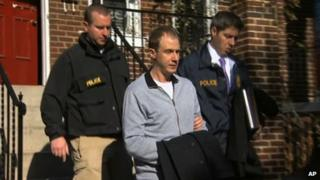 Jesse Ryan Loskarn (centre) was led away from his Washington DC home by authorities on 11 December 2013