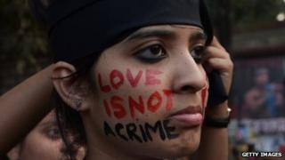 "An Indian gay-rights protester has ""love is not a crime"" written on her face."