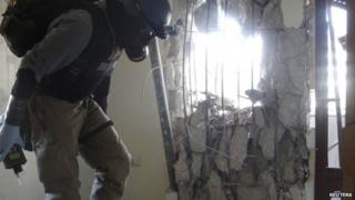 """A UN chemical weapons expert, wearing a gas mask, inspects one of the sites of an alleged chemical weapons attack in the Damascus"""" suburb of Zamalka"""