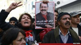 A member of the main labour union body UGTT holds a poster of assassinated secular opposition leader Chokri Belaid during a protest calling for the government led by the Islamist Ennahda party to step down, in Tunis December 4, 2013