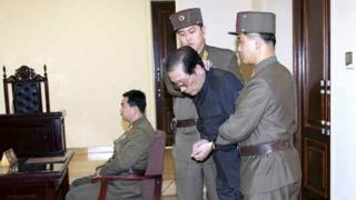 Jang Song Thaek, with his hands tied with a rope, is dragged into the court by uniformed personnel in this December 13, 2013 picture taken from Rodong Sinmun December 12, 2013 and released by Yonhap.