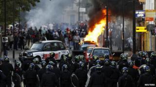 Rioters and police in London in 2011