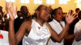 """Member of a local choir sing and dance during a memorial service for Nelson Mandela at the Komkhulu or """"Great Place"""" in Mvezo."""