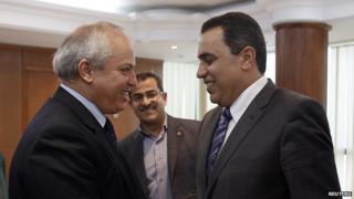 Mehdi Jomaa (R) shakes hands with Libyan Oil Minister Abdelbari al-Arusi in Tunis April 12, 2013