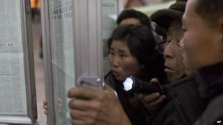 A North Korean man uses a flashlight as he and other commuters gather around a public newspaper stand in Pyongyang, North Korea, on 13 December 2013
