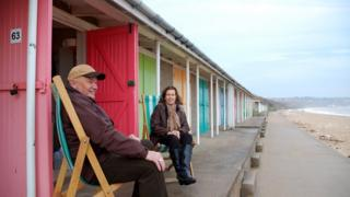 Roger and Sheila Widdup sat on deckchairs outside their beach hut
