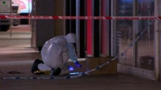 Forensic investigators examined a cardboard box outside the Golf Madness store