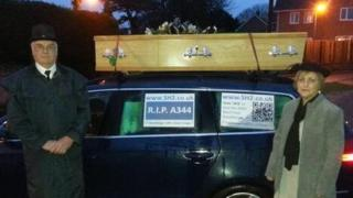 Campaigners against traffic levels on the A303 in Wiltshire drive a coffin mounted on a car