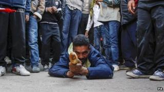 A man uses bread to mark the third anniversary of the Arab Spring in Tunisia, 17 December 2013