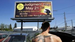 Mose Macdonald works in the impound yard of Stealth Recovery and Towing in Eugene, Oregon near a billboard proclaiming the upcoming judgment day 19 May 2011