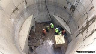 Workers in storm drain as tunnel machine breaks through
