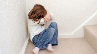 Young girl covering her face in a corner