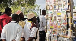 Zanzibaris scan the papers at a newsstand in Stone Town