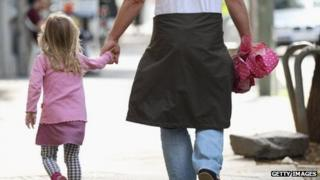 A German man walks hand-in-hand with a little girl.