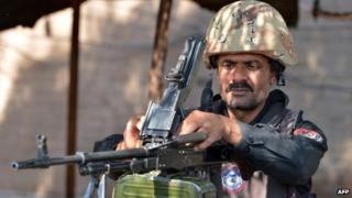 A Pakistani policeman loads his gun at a security check point in northern Pakistan (November 2013)