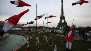 Kites in the shape of Father Christmas glide in the wind next to the Eiffel Tower in Paris
