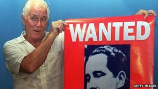 Train-robber Ronnie Biggs holds up his wanted poster in 1994.