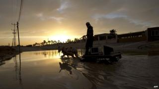 A Palestinian man stands on his cart laden with two computer screens as he leads his donkey through rain floods in Gaza City (December 17, 2013)