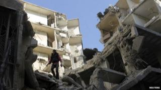 A man stands on a destroyed building in Aleppo's Sukkari district (24 December 2013)