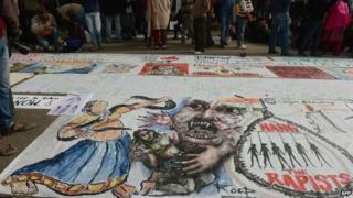 "In this photograph taken on December 30, 2012, Indian bystanders look at a banner featuring images of ""government and rapists"" as it lies on a road in New Delhi"
