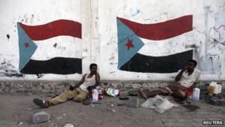 Men sit beside painted flags of the former South Yemen in Aden (August 2013)