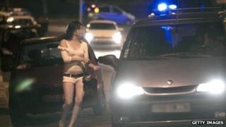 A prostitute approaches a car in Paris.