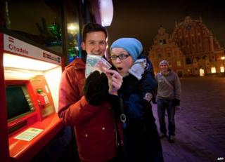 A man and woman withdraw euros from a cash machine in Riga, 1 January